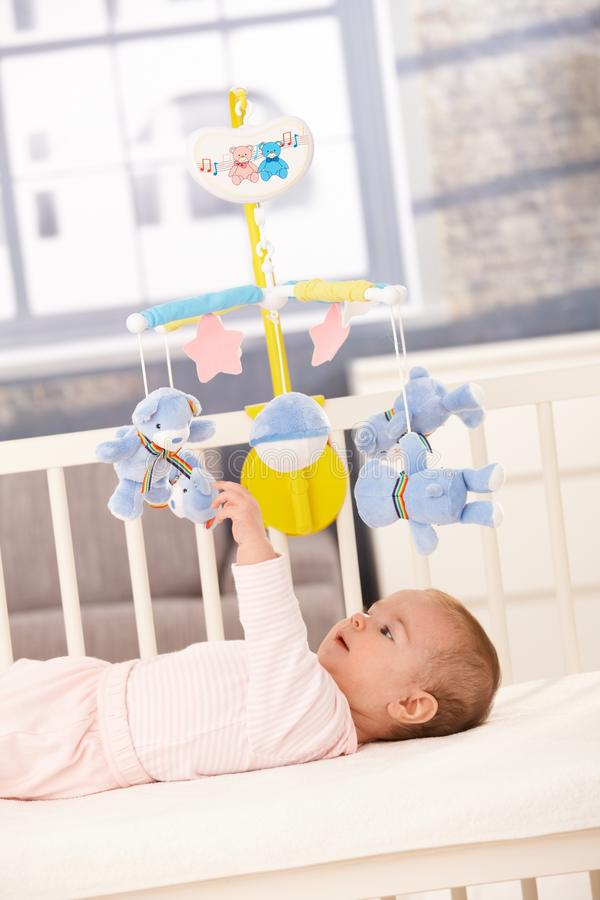 Baby playing with bed mobile. Toy, reaching up to teddy bear royalty free stock photo