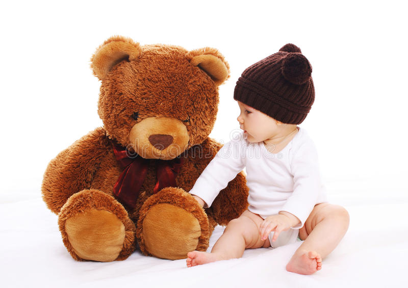 Baby playing with big teddy bear toy on white. Background royalty free stock photos