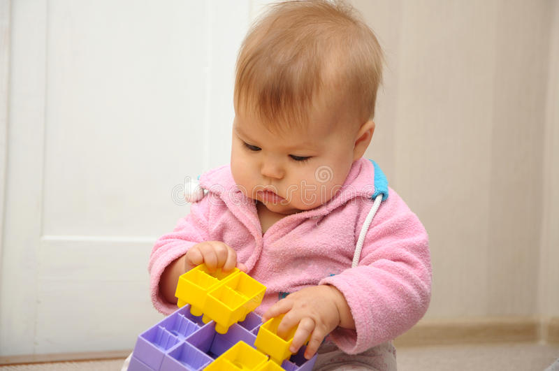 Baby playing with colored constructor stock photos