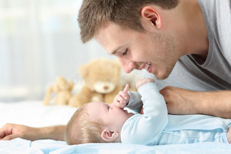 Baby playing with his father stock images