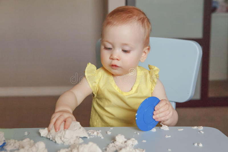 Baby playing kinetic sand. Portrait of funny cute white Caucasian baby playing kinetic sand indoors at kindergarden. Early creativity brain development concept royalty free stock photo