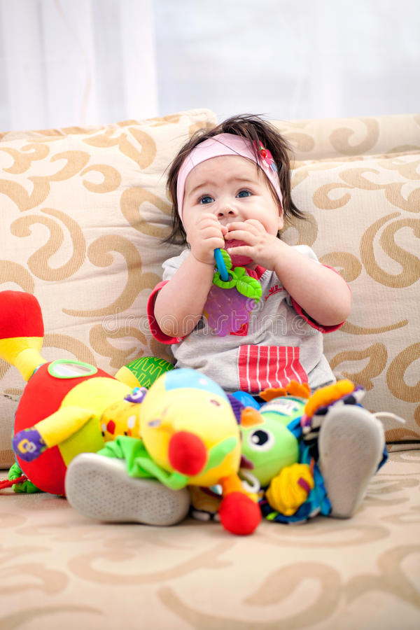 Baby is playing in the living room on the couch with toys royalty free stock image