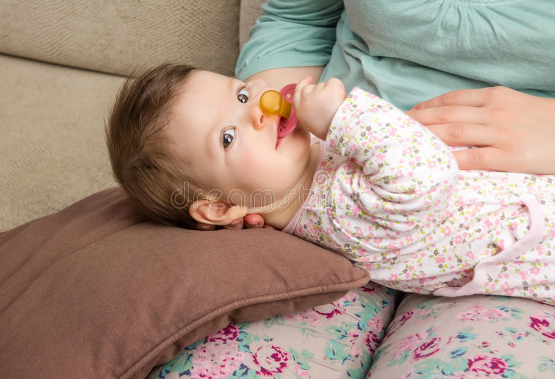 Baby playing with pacifier lying over mother legs. Adorable baby playing with the pacifier lying in her mother legs at home royalty free stock image