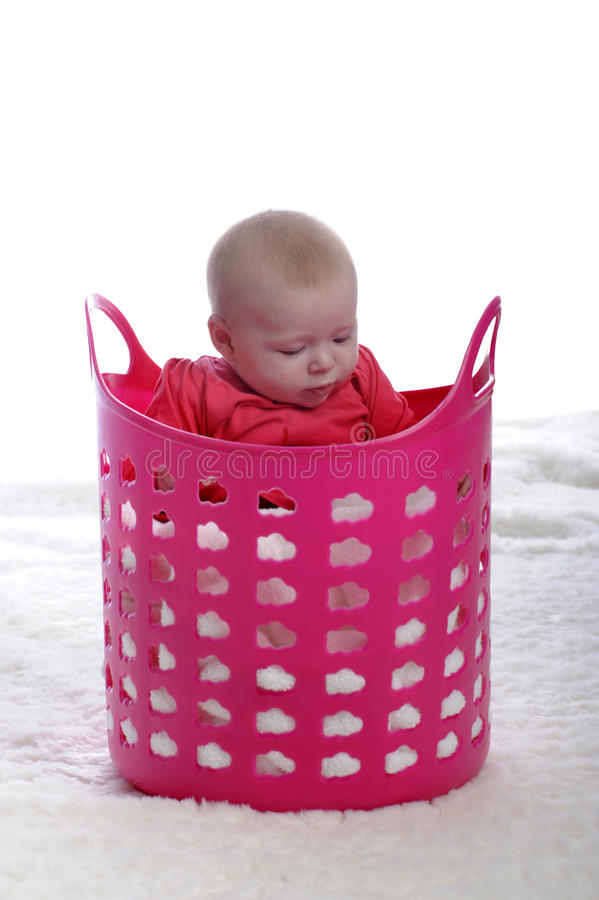 Baby playing in pink plastic laundry basket