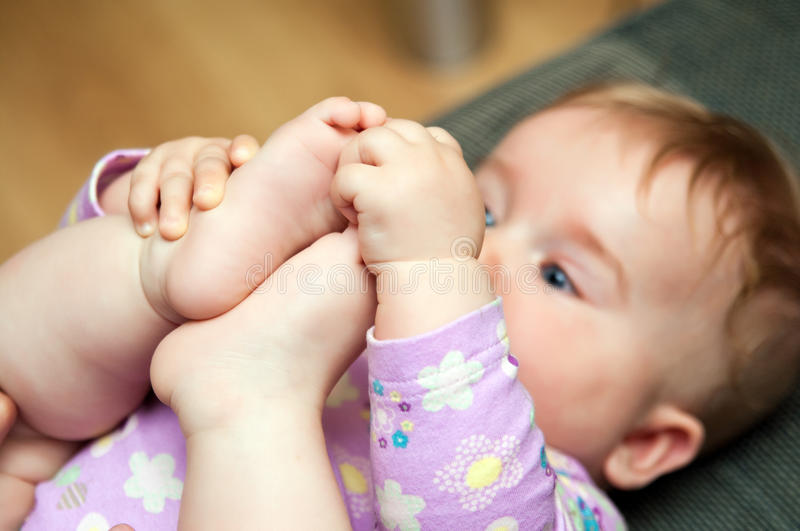 Baby playing with toes stock photo