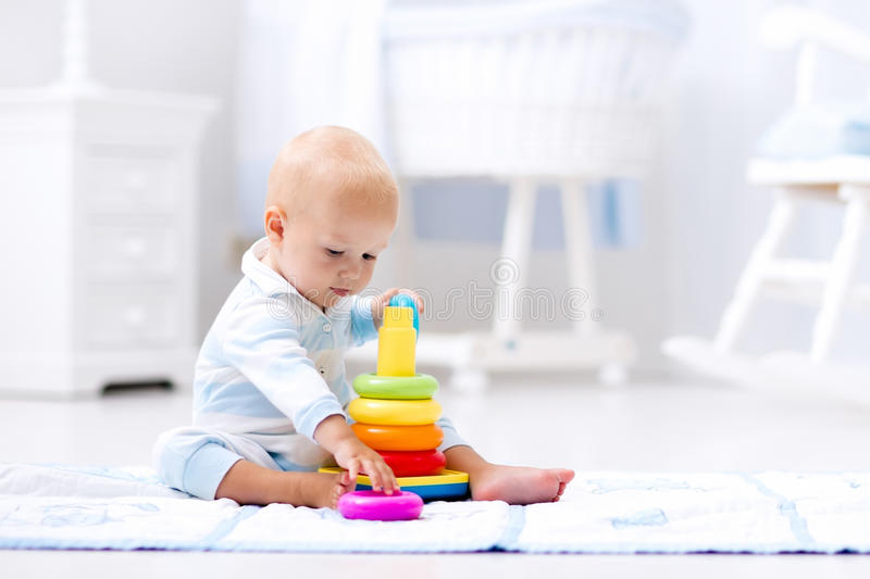 Baby playing with toy pyramid. Kids play royalty free stock photography