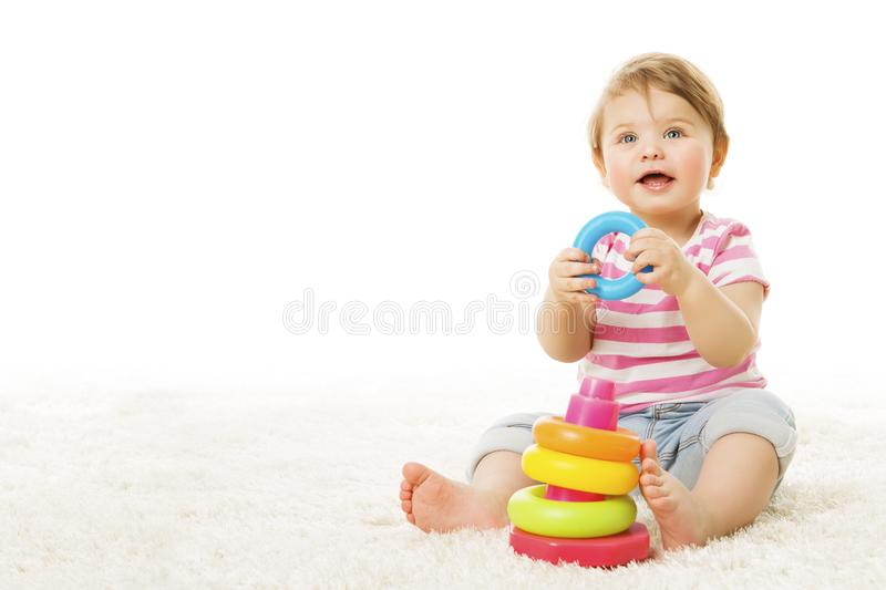 Baby Playing Toy Rings, Infant Child with Colorful Pyramid. Baby Playing Toy Rings, Infant Child with Colorful Circle Pyramid, Happy Kid on Carpet over White stock photo