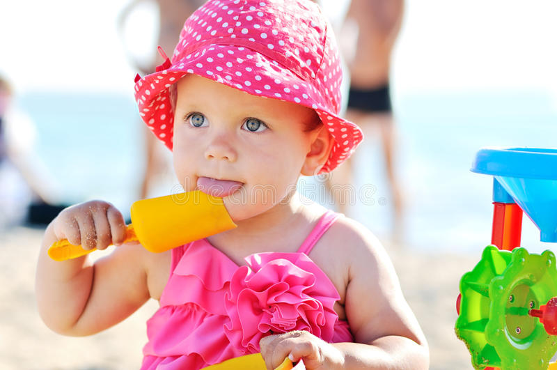 Baby playing toys on beach. Cute baby girl on the beach royalty free stock image