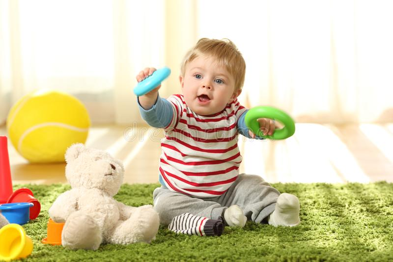Baby playing with toys on a carpet stock photo