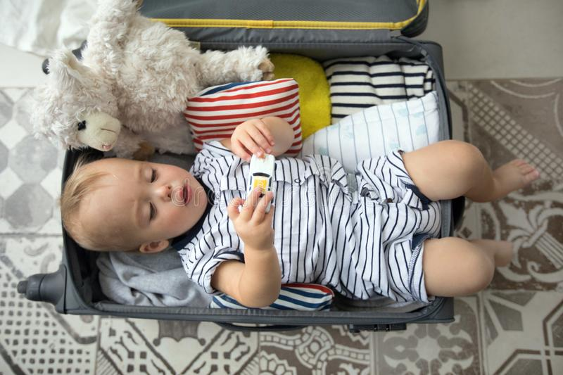 Baby playing with toys in suitcase. From above cute baby boy playing with toy car while lying in open suitcase near plush sheep before going on vacation stock photo