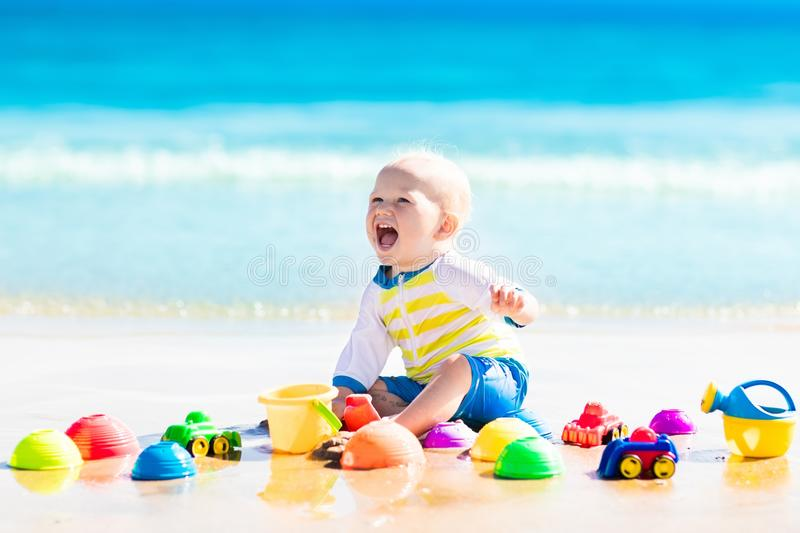 Baby playing on tropical beach digging in sand. Cute laughing baby boy wearing sun protection rash guard playing with bucket and shovel on tropical beach during royalty free stock photo