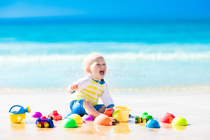 Baby playing on tropical beach digging in sand. Cute laughing baby boy wearing sun protection rash guard playing with bucket and shovel on tropical beach during royalty free stock photos