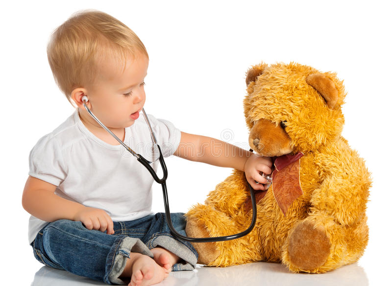 Baby plays in doctor toy bear, stethoscope. Baby plays in doctor toy bear and stethoscope stock photo