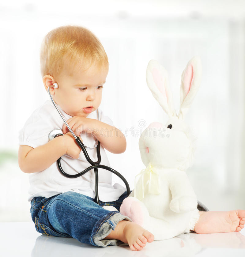 Baby plays in doctor toy bunny rabbit and stethoscope. Cute baby plays in doctor toy bunny rabbit and stethoscope royalty free stock image