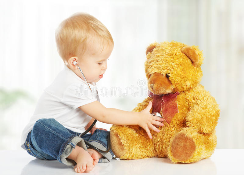 Baby plays in doctor toy teddy bear and stethoscope royalty free stock image