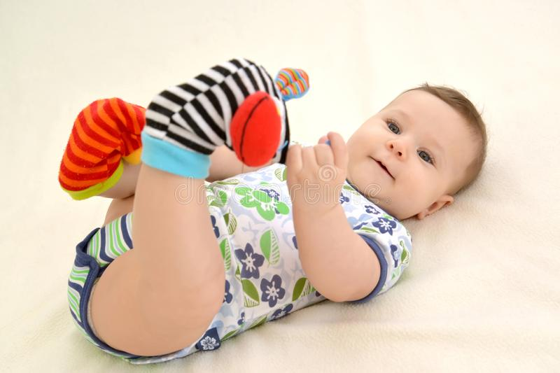 The baby plays legs in color socks with rattles stock photography