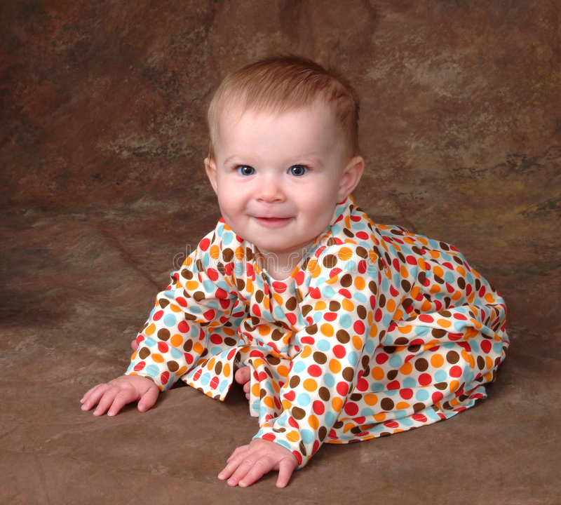 Baby in Polka Dot Dress. Baby in sitting position, leaning forward to keep her balanced, dressed in a polka dot dress stock photography
