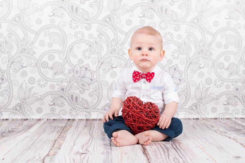 Baby poserar med röd hjärta royaltyfria bilder