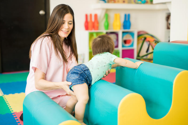 Baby practicing crawling at a school. Baby and her therapist working on some crawling and climbing exercises in a therapy and stimulation center stock image