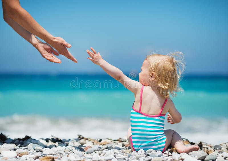 Baby pulling hands to mother. Baby girl pulling hands to mother stock image