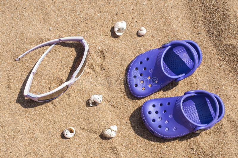 Baby purpere belemmering en zonnebril op het zand op het strand Leuke details van de zomervakantie Babyschoenen op het strand stock afbeelding