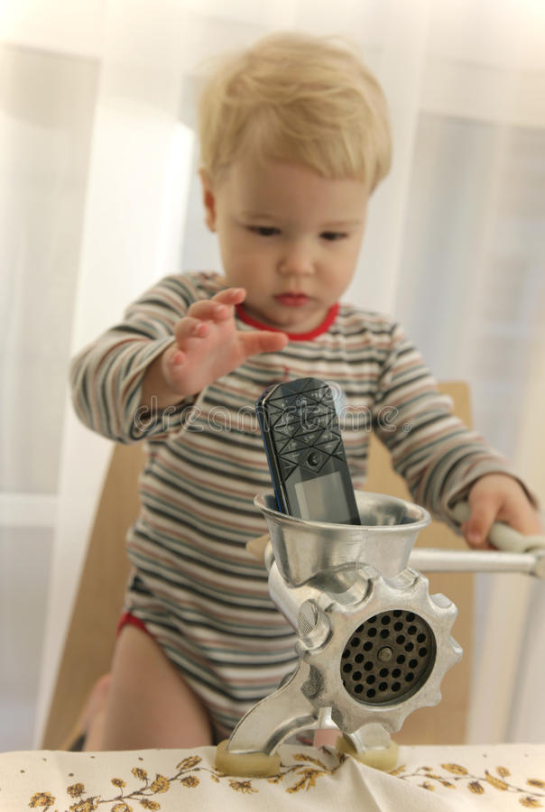 Baby Pushed In Mobile Telephone In Meat Grinder Royalty Free Stock Image