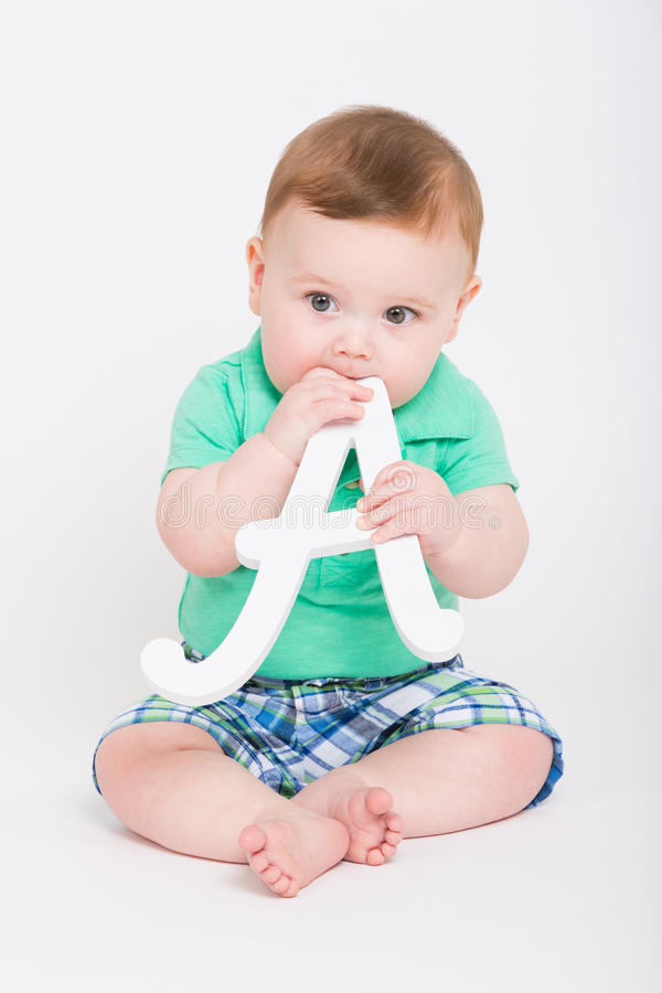 Baby Puts Letter A in His Mouth stock photo