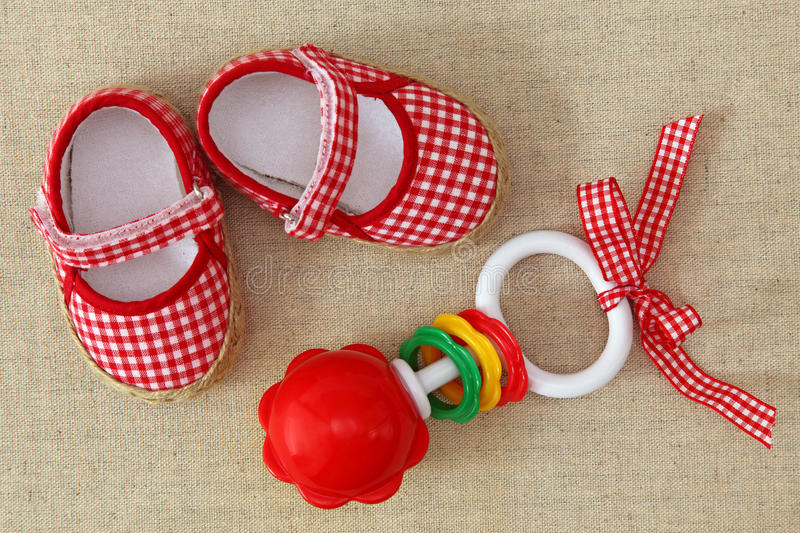 Baby rattle and red shoes. On brown background royalty free stock photos