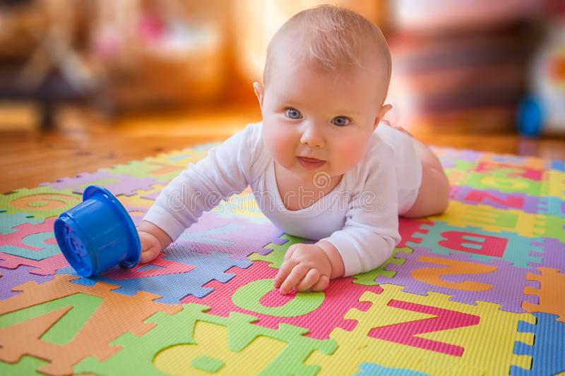 Baby reaching cup on alphabet mat royalty free stock image