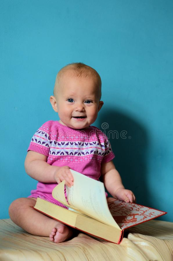Baby reading. Little baby girl in a pink dress reading classical literature stock image
