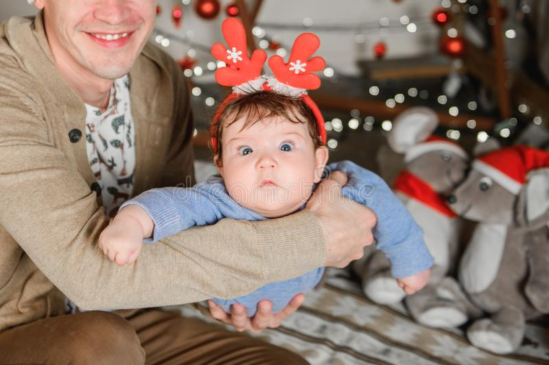 Baby in red deer horns. happy New Year. a childs suit. Christmas. father holds in his arms and shakes from side to side royalty free stock photos
