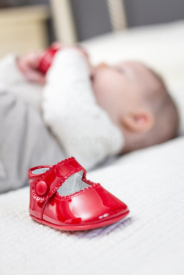 Baby red shoes and babe playing on the background. Closeup of baby red patent leather shoes over a bed and adorable babe playing on the background stock images