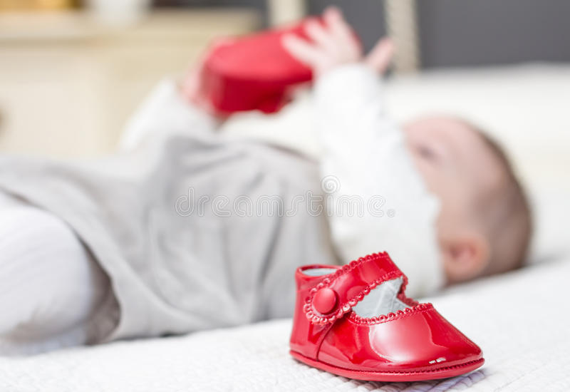 Baby red shoes and babe playing on the background. Closeup of baby red patent leather shoes over a bed and adorable babe playing on the background stock image