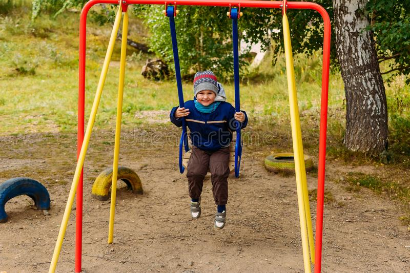 Baby rides on children`s swings. Outdoors royalty free stock images