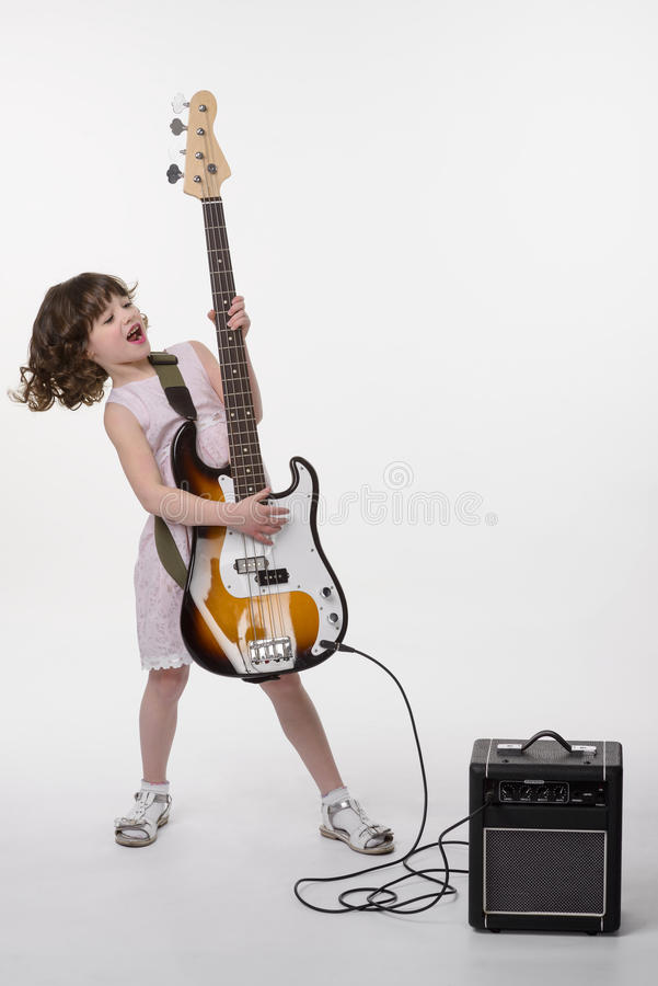 Baby rocks with opened mouth. Baby rocks when she holds her bass guitar connected to its amp. Full body shot. Delighted young child with an opened mouth holds royalty free stock images