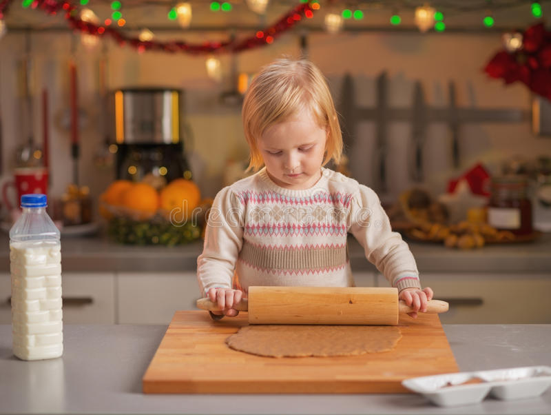 Baby rolling pin dough in christmas decorated kitchen royalty free stock image