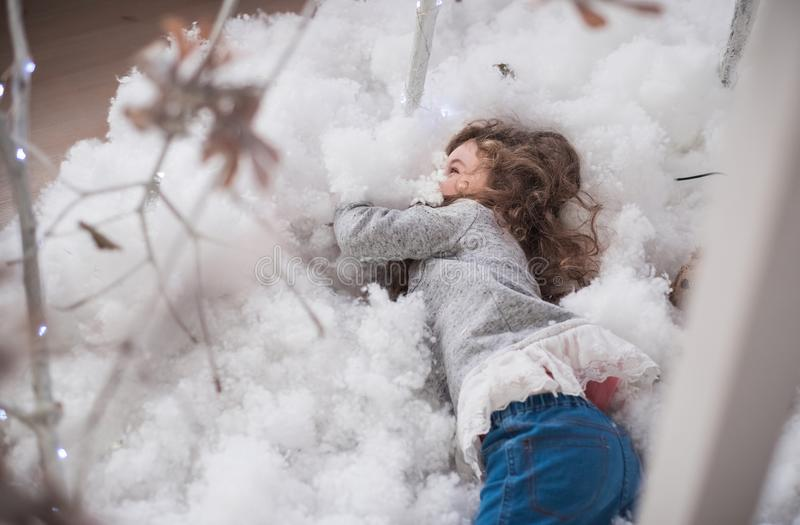 The baby rolls in artificial snow. Winter fun in the children`s room royalty free stock image