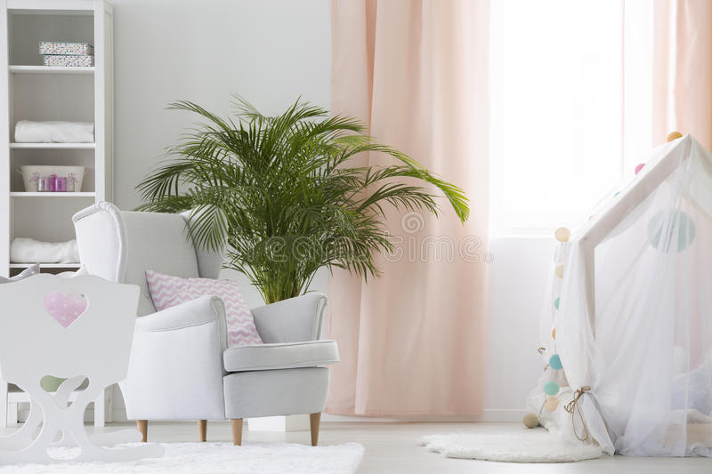 Baby room with armchair, crib and plant. White modern baby room with armchair, crib and plant royalty free stock images