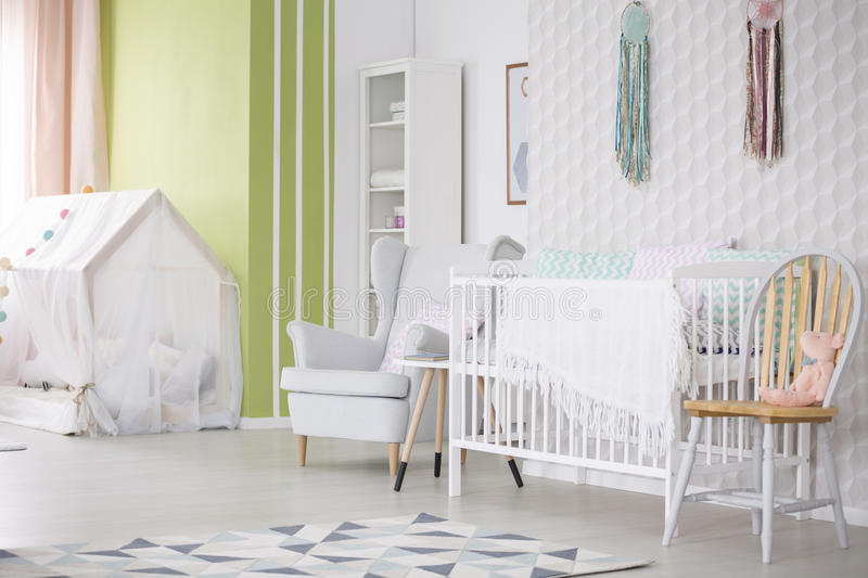Baby room with chair, armchair and crib. White and green baby room with chair, armchair and crib royalty free stock photography