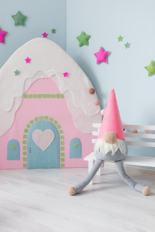 Baby room decoration, toy home and textile dwarf, stars on blue wall stock photography