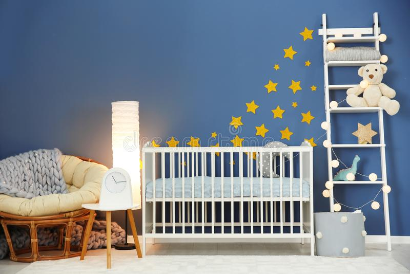 Baby room interior with comfortable crib. And papasan chair stock photos