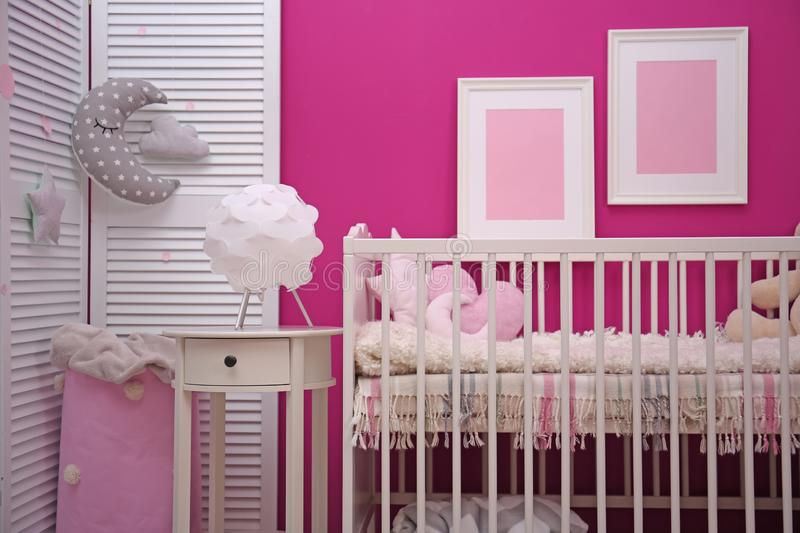 Baby room interior with crib near. Color wall royalty free stock photography