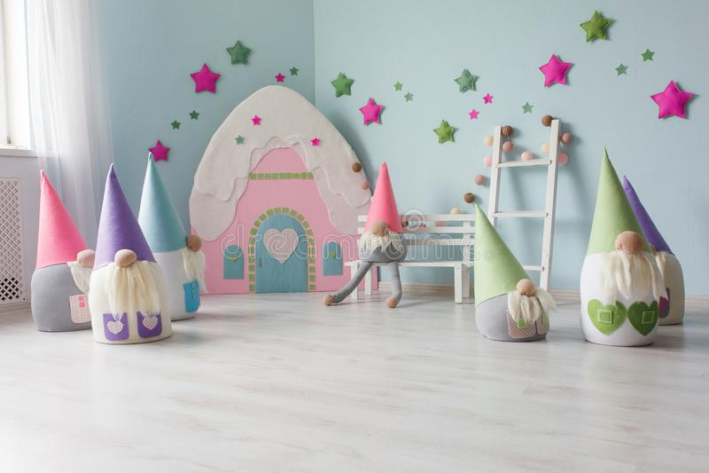 Baby room interior with toy house and textile dwarfs. Light pastel colors stock images