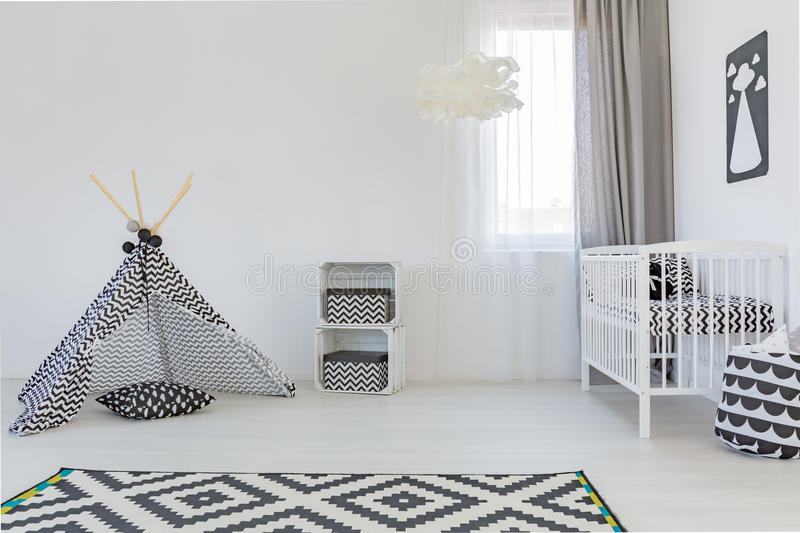 Baby room with white cot. Light baby room with white cot, carpet and play tent royalty free stock image