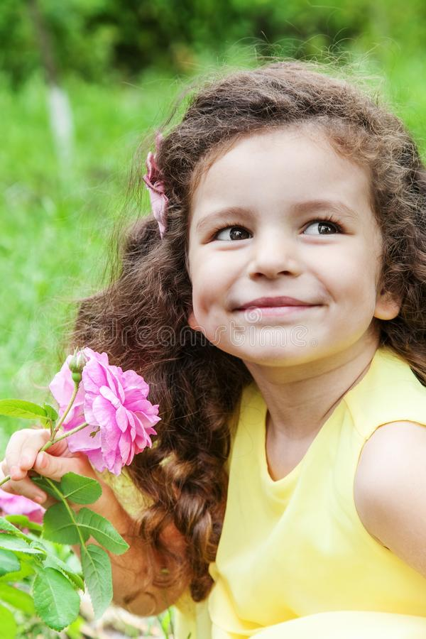 Baby with rose flower outdoors stock photo