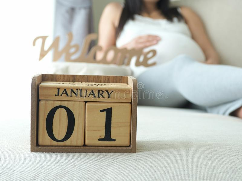 Baby ` s Abgabefrist Datum neuen Jahres am Kalender mit Hintergrund der schwangeren Frau lizenzfreie stockfotografie