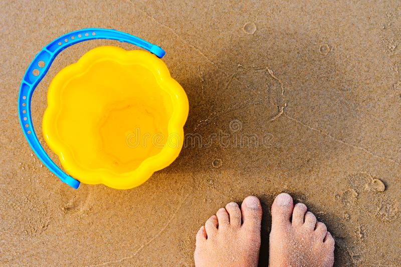 Baby`s bare feet on a golden sandy beach next to a yellow toy bucket. Vacation concept royalty free stock photo