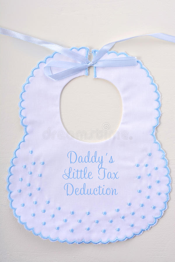 Baby's bib with Tax Day message. Baby's bib on white wood background, with Tax Day message, Mommy and Daddys Little Tax Deduction royalty free stock image