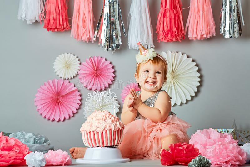Baby`s first birthday. Cute baby tasting the birthday cake stock images