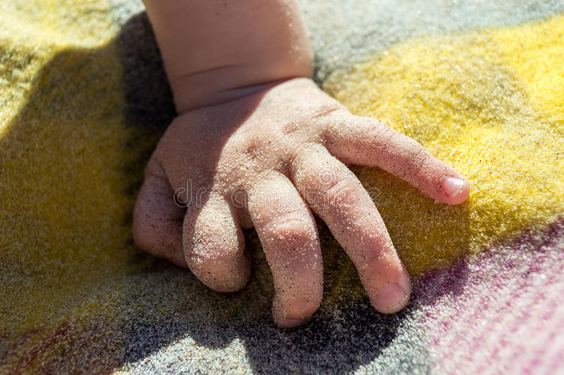 Baby's hand in sand on the beach. Summer beach background. Baby's hand in sand on the beach. Summer beach background royalty free stock images